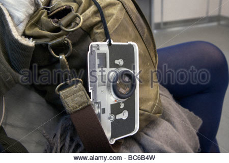 traditional Leica range finder camera hanger on a backpack bag - Stock Photo