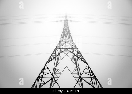 Looking up at an electricity pylon through the mist - Stock Photo