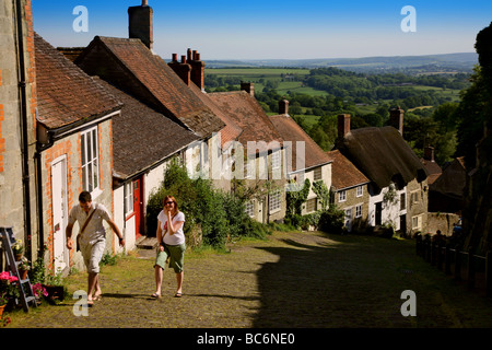 A couple walking up the famous cobbled street on Gold Hill in Shaftesbury - Stock Photo