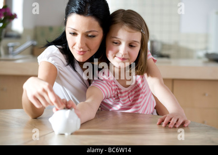 Mother and daughter with piggy bank - Stock Photo