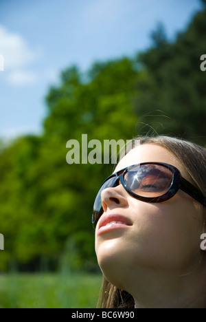 Young woman sunbathing in meadow - Stock Photo