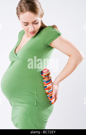 pregnant woman with hot water bottle - Stock Photo