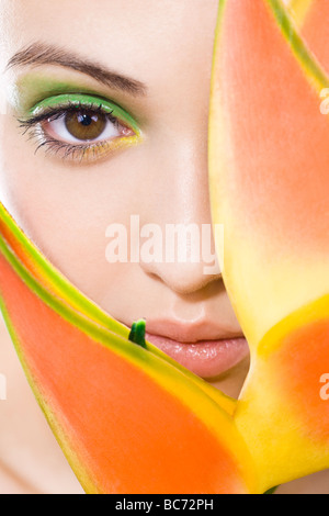 woman with green makeup and plant next to face - Stock Photo