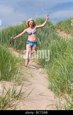 Attractive young woman in twenties runs down a sand dune. Crosby Beach, Liverpool, Merseyside, United Kingdom. - Stock Photo