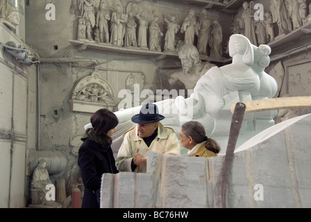 plaster casts and contemporary sculpture surround owner Carlo Nicoli and guests at the Nicoli Sculpture Studios - Stock Photo