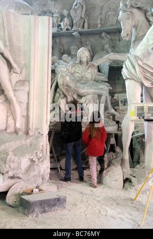 Children pause in wonder at a sust covered plaster model of Michelangelo's Pieta in the Nicoli Sculpture Studios - Stock Photo