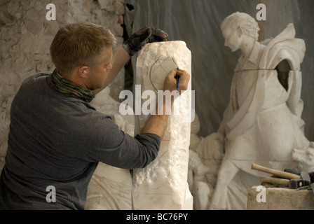 A sculptor draws on a block of stone as he carves in the Nicoli Sculpture Studios carrara - Stock Photo