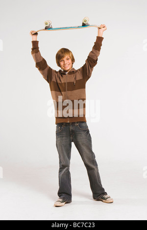 Teenage boy (13-14) holding skateboard over head, smiling - Stock Photo