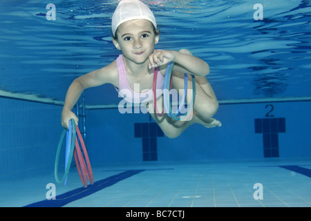 Underwater picture of a girl swimming and playing with toys - Stock Photo