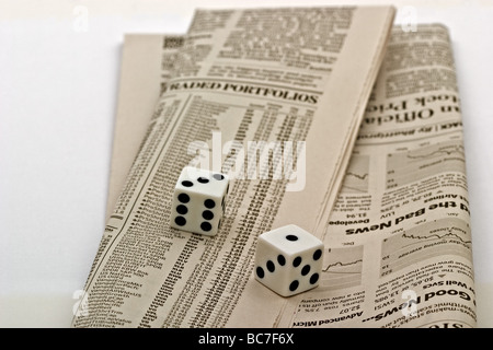 Dice on top of a the Stock market listing section of a newspaper - Stock Photo
