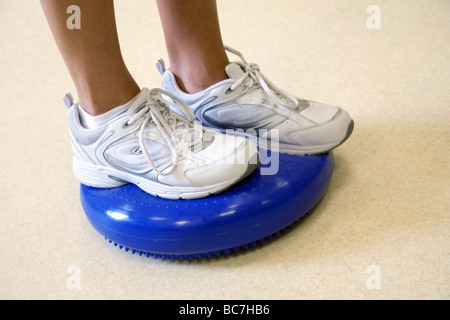 Close up of person exercising on a wobble cushion - Stock Photo