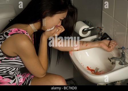 glamorous teenage girl self harming in toilet - Stock Photo