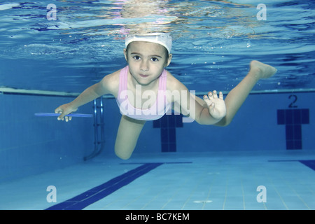 Underwater picture of a girl swimming and playing with joy - Stock Photo