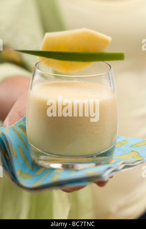 Woman serving a glass of mango lassi (India) - - Stock Photo