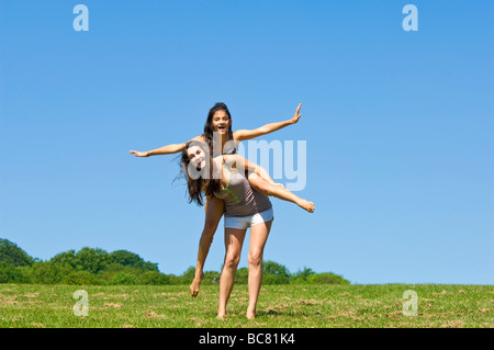 Horizontal portrait of two teenage girls having fun having a piggy back ride in a park on a bright sunny day - Stock Photo