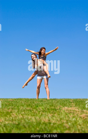 Vertical portrait of two sisters outside having a piggy back ride on a bright sunny day - Stock Photo