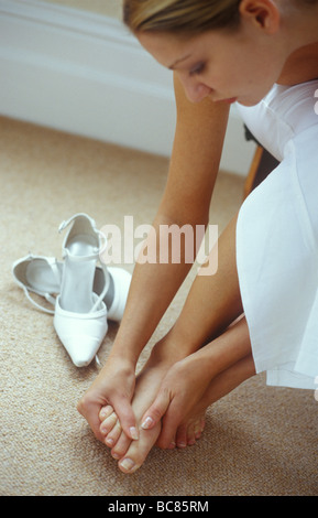 woman massaging her foot as if it is painful after wearing high heels - Stock Photo