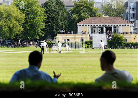Onlookers watching a match during lunch break at Trinity College cricket club grounds in central Dublin Republic - Stock Photo