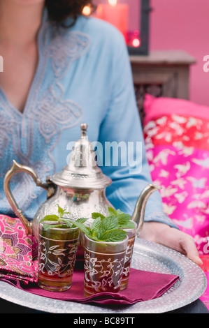 Woman serving peppermint tea on tray - - Stock Photo