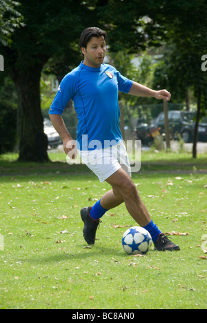 footballer in the park dribbling a ball - Stock Photo