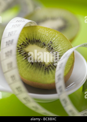 Half a kiwi fruit with tape measure - - Stock Photo