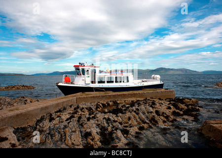 MV Ossian of Staffa at the jetty at Clamshell Cave on the isle of Staffa with the Isle of Mull in the background - Stock Photo