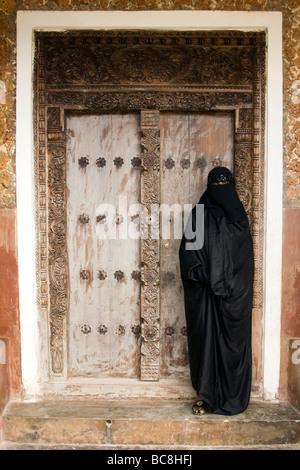 Woman standing in ornate doorway - Lamu Island, Kenya - Stock Photo