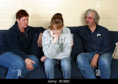Teen years : Defiant teenage girl sit on the sofa between angry parents - Stock Photo