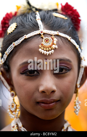 An East Indian or Hindu girl wearing traditional dress and headdress at a festival. - Stock Photo