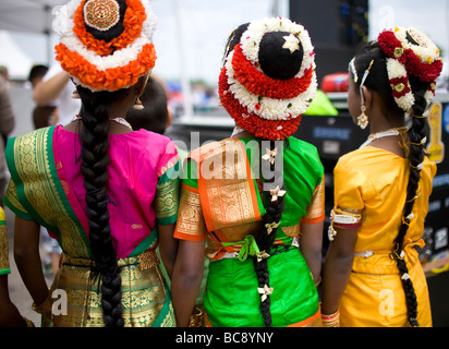 Three East Indian or Hindu girls wearing traditional headdresses waiting to perform at a festival. - Stock Photo