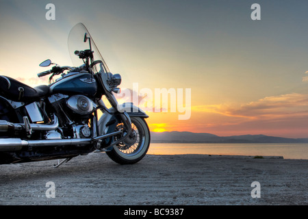 A harley davidson motorbike motorcycle taking in the sunset as the sun goes down on the day - Stock Photo
