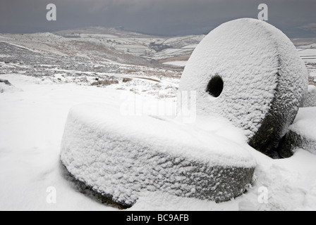 Snow covered abandoned millstones at Stanage Edge in winter - Stock Photo