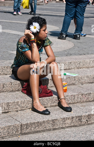 pretty brown skinned girl wearing blue nails and a large fresh flower in her curly dark hair, sitting in Union Square, - Stock Photo