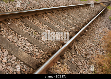 Two rusty rail tracks on gravel with some grass - Stock Photo