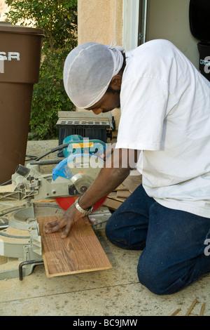 Man cuts wood laminate for home flooring MR  © Myrleen Pearson - Stock Photo