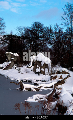 Victorian models of group of dinosaurs in snow around Crystal Palace Park lake South London England - Stock Photo
