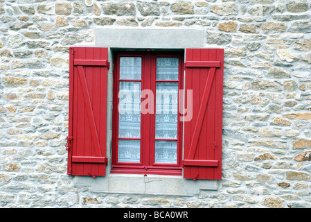 Bright red window shutters and nautical net curtain on house, Roscoff, Brittany, France - Stock Photo