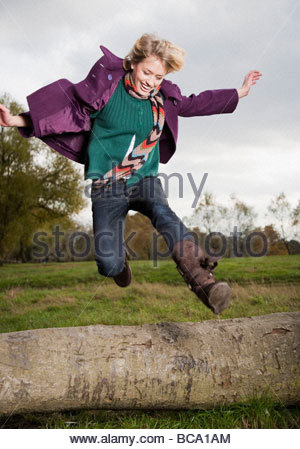 Woman jumping over log in field - Stock Photo