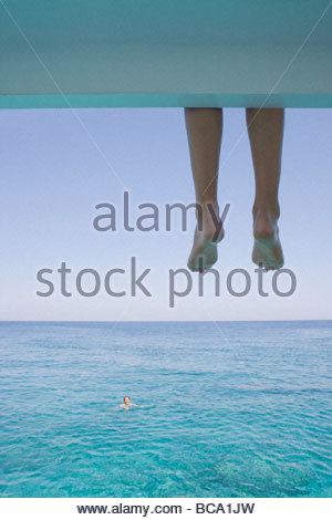 Boy watching man swimming in ocean - Stock Photo