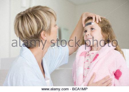 Woman taking daughter's temperature - Stock Photo