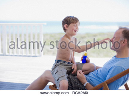 Son sitting in father's lap on deck - Stock Photo