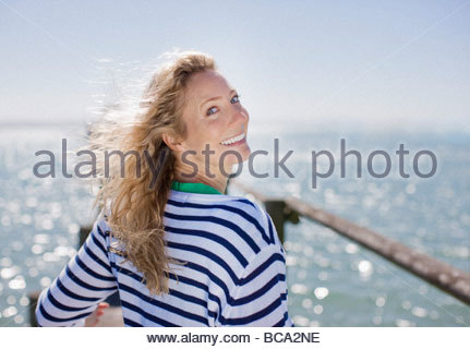 Woman smiling on pier by ocean - Stock Photo