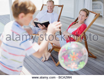 Parents watching son play with ball on deck - Stock Photo