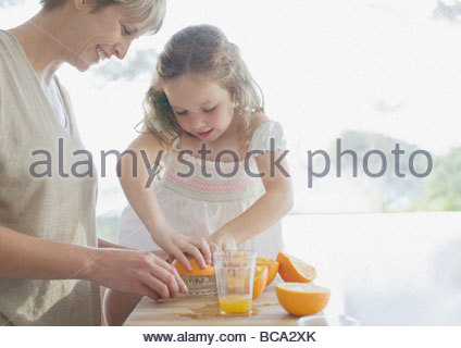Mother and daughter squeezing oranges - Stock Photo