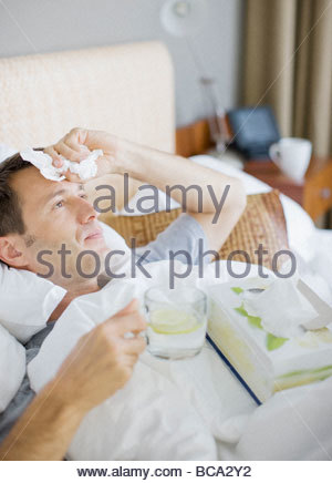 Man sick in bed drinking hot drink - Stock Photo