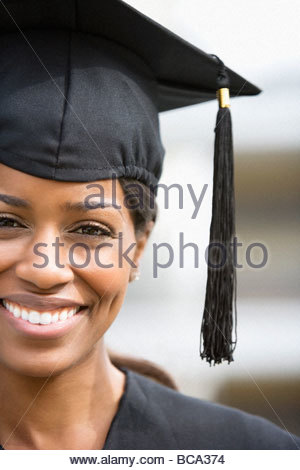 Smiling woman in graduation cap and gown - Stock Photo