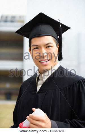 Man in graduation cap and gown holding diploma - Stock Photo