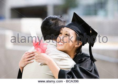 Man hugging graduate holding diploma - Stock Photo