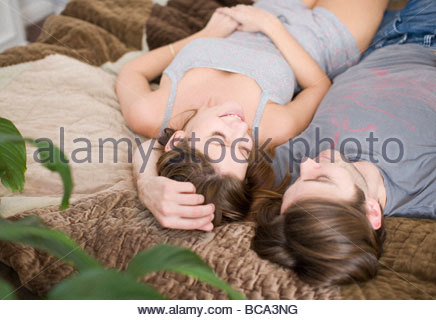 Couple laying on bed together - Stock Photo