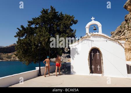Couple sitting in front of Saint Paul's Chapel, Saint Paul's Bay (Agios Pavlos), Lindos, Rhodes, Greece - Stock Photo